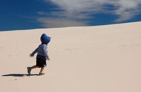 Toddler walking up sand dune