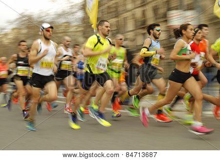 BARCELONA - FEB, 15: Group of runners in Barcelona streets running during Barcelona Half Marathon in Barcelona on February 15, 2015 in Barcelona, Spain.