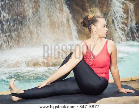 Woman practicing yoga near waterfall. Sage Twist.