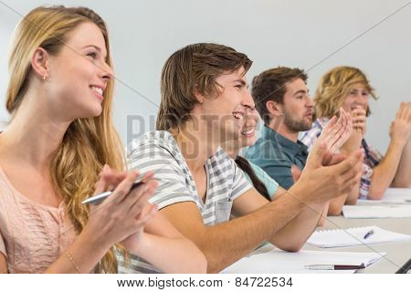 Side view of students clapping hands in classroom