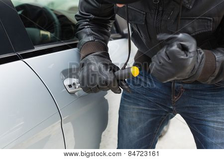 Thief breaking into car with screwdriver in broad daylight