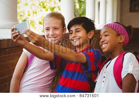 Portrait of happy little school kids taking selfie in school corridor