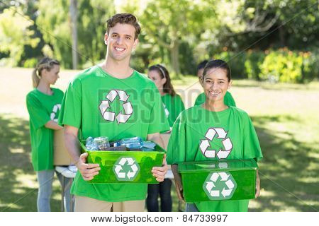 Happy environmental activists in the park with recyclables on a sunny day