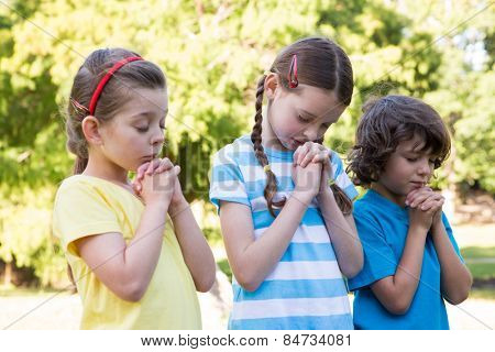 Children saying their prayers in park on a sunny day poster