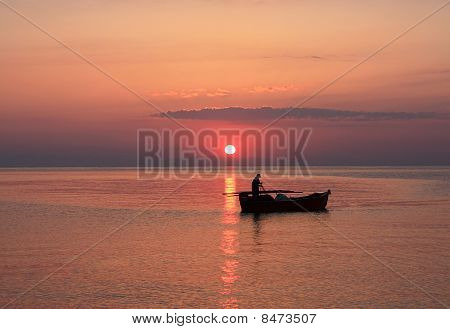 The Setting Sun Silhouettes Fishermen In A Boat