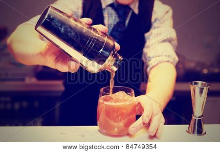 Bartender is making cocktail at bar counter, toned image poster