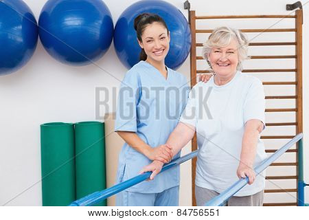Senior woman and therapist looking at camera in fitness studio