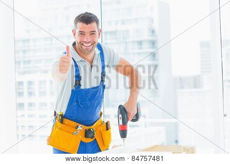 Portrait of happy handyman drilling hole in plank while gesturing thumbs up in bright office