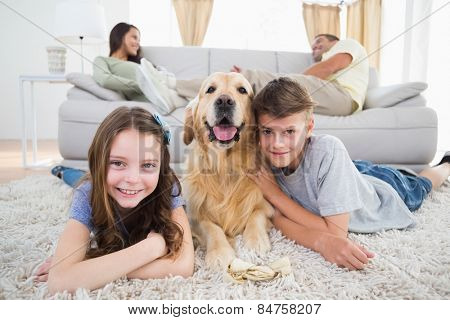 Portrait of happy siblings lying with dog while parents resting on sofa at home
