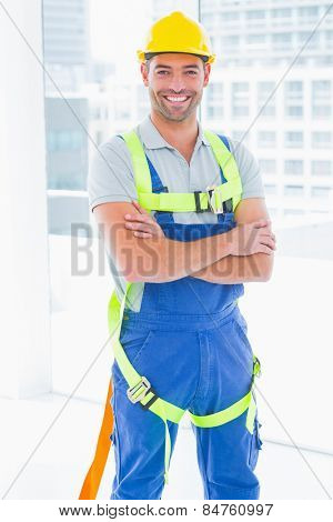 Portrait of happy manual worker wearing safety harness standing arms crossed in bright office