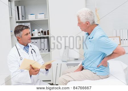 Male doctor discussing reports with senior patient suffering from backache in clinic