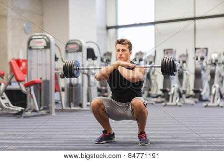 sport, bodybuilding, lifestyle and people concept - young man with barbell doing squats in gym poster