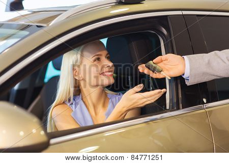 auto business, car sale, consumerism and people concept - happy woman taking car key from dealer in auto show or salon