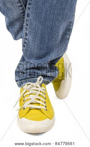 Flashy yellow canvas sneakers and jeans.