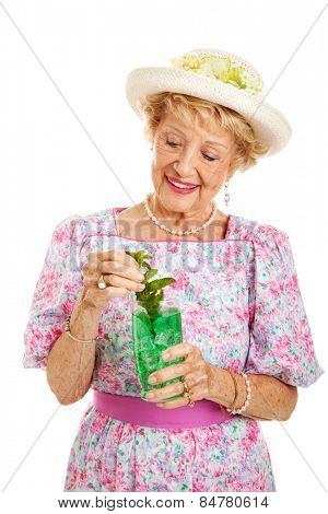 Southern senior lady dressed for the Kentucky Derby and drinking a mint julep.  Isolated on white.