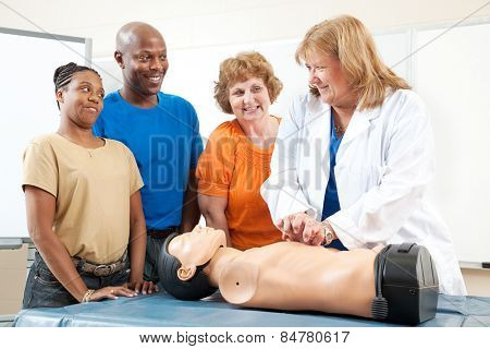Adult education class, teaching first aid CPR using a state of the art doll.