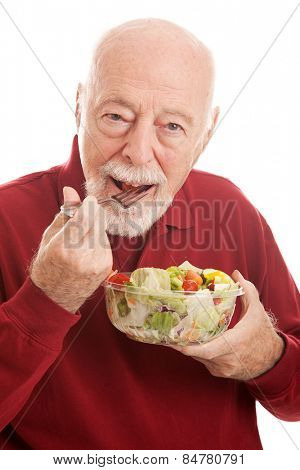 Fit senior man eating a healthy salad for lunch.  White background.