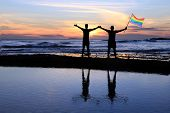 Silhouette of a gay couple holding a rainbow pride flag at sunset.  poster