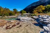 Rocky River Bed of the Crystal Clear Frio River.  Fall foliage on Bald Cypress Trees. poster