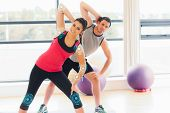 Two people doing power fitness exercise at yoga class against fitness interface poster