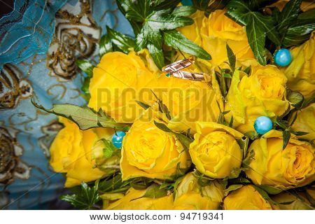 Two Gold Wedding Rings And Yellow Roses