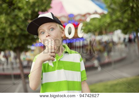 Cute boy fully enjoying an ice cream cone during a summer carnival or fair. He is making an excited expression