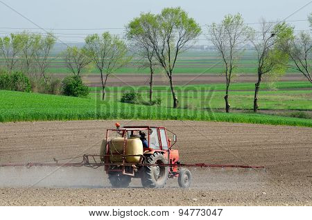 Tractor Sprinkling Pesticides Againt Bugs On Plowed Land On Sunny Spring Day