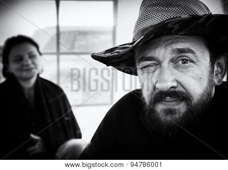 Black and white portrait of a bearded man in a broad-brimmed hat and a woman in the background