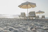 Sunset sandy beach on Greek Kos island with parasols and sunbeds poster