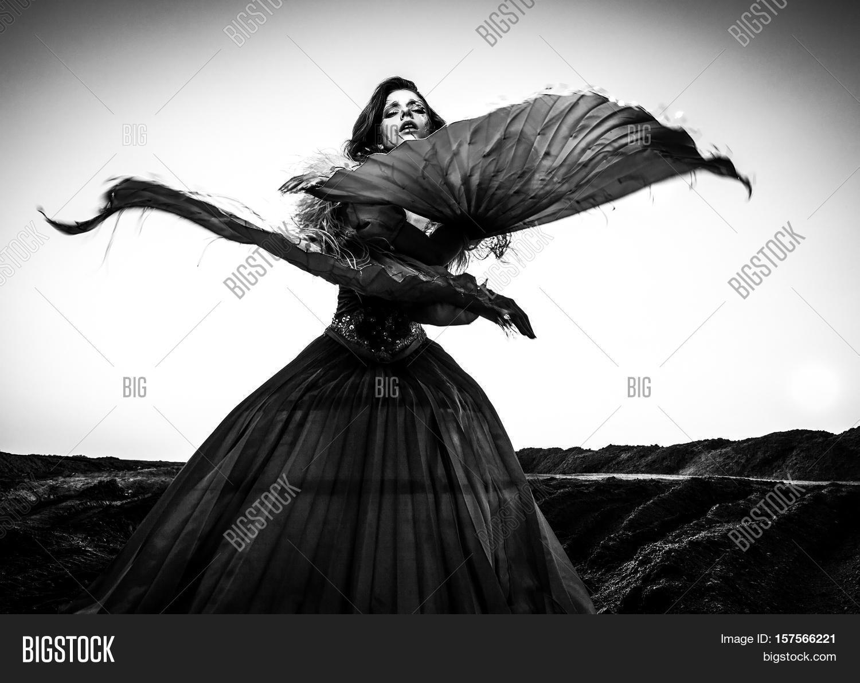 Black white fine art portrait of attractive romantic woman at fairy tale dry field