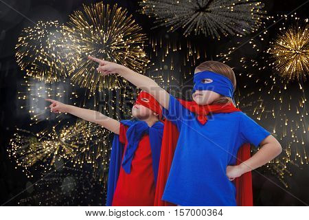 Masked kids pretending to be superheroes against colourful fireworks exploding on black background