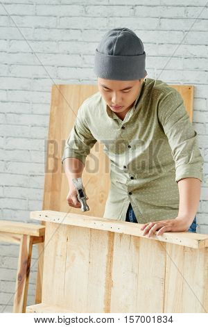 Asian professional joiner making wooden table top
