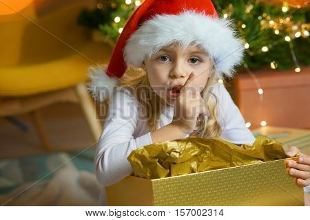 Portrait of cute little girl keeping a secret on Christmas eve