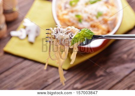 Pasta with mushrooms sauce impaled on fork, closeup