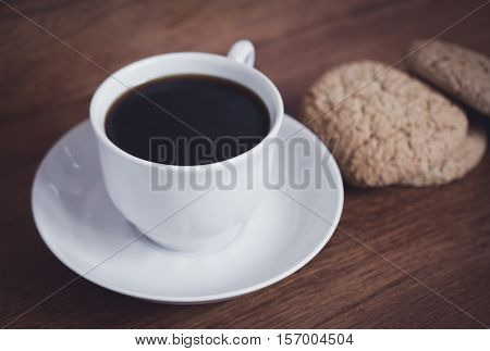 one fresh cup of coffee and biscuits for breakfast on a wooden table