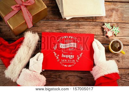 Santa claus holding a red placard against christmas greeting