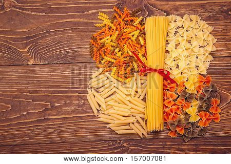 Spaghetti Tied With A Red Ribbon, A Number Of Different Types Of Pasta, Lying Around On Retro Wooden