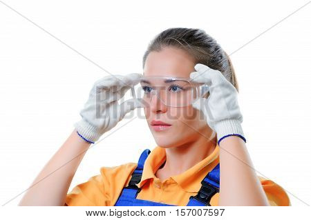 Female painter in safety glasses and coveralls posing on white background.