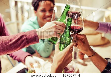 Diverse People Ethnicity Friends Hanging Out - Multiracial Dinner Contest With Food and Alcohol - Chill and Relax Concept - Pink Vintage Warm Filter - Focus On Bottom Bottle Hand