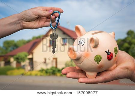 Real estate agent giving flat keys to a new property owner who is paying last saving money from piggy bank on blurred background