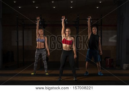 Group of caucasian athletes doing exercises with kettlebell in gym. Sports fitness workout.