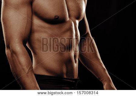 Muscular fitness model with sexy body posing shirtless. Male athlete with naked torso and six packs.