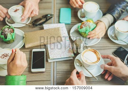 People hands drinking cappuccino and eating muffins at bar coffee shop - Young friends doing breakfast with upper point of view - Socializing concept - Soft focus on bottom hand - Soft vivid filter