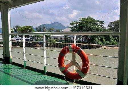 Plastic orange saving belt by the railing fence of the ferry to Samui island, Thailand.