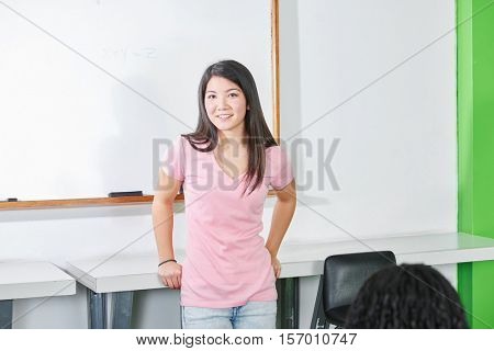 Student in front of a blackboard in a classroom with a smile