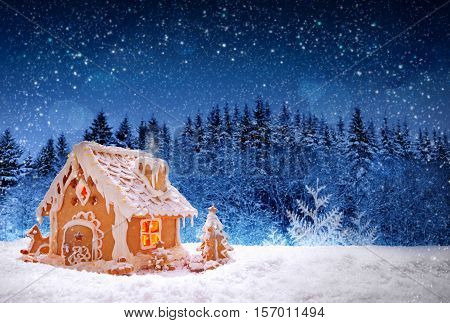 Gingerbread house isolated on fir trees forest background. Christmas card with snowfall and luminous house in the forest.