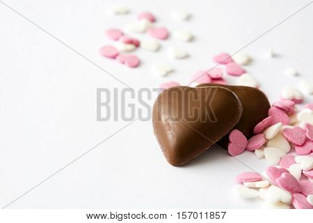 Chocolate bonbons with heart shape and candies on white background