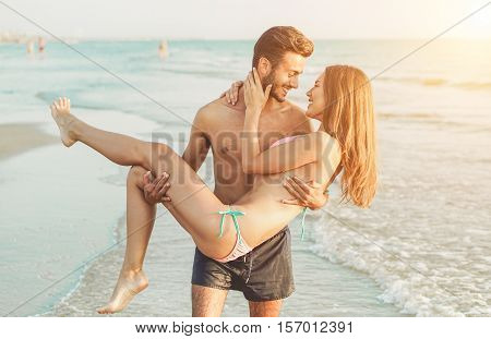 Young couple having tender moments and kissing on the beach at sunset - Man lifting handsome woman in their first vacation together - Love concept - Warm vintage filter