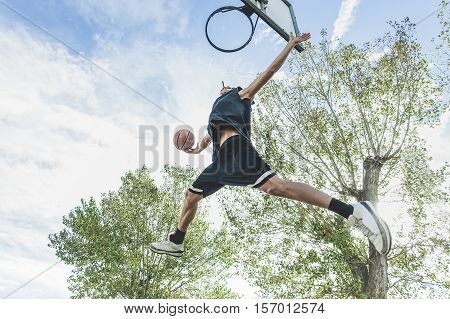 Basketball player performing huge slam dunk on the court in urban grunge camp with back light - Yong athlete in action outdoor - Sport concept - Original sunlight - Soft warm raw filter
