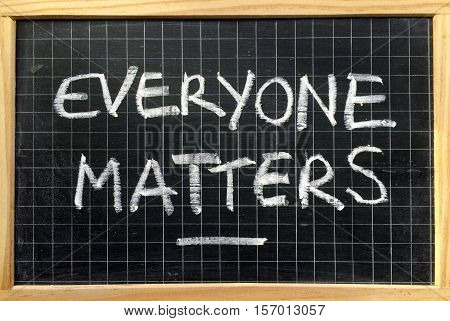 The phrase Everyone Matters written by hand in white chalk on a used blackboard as a reminder of equality for all